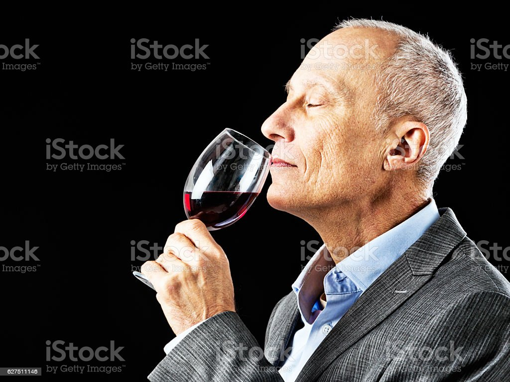 Mature man sniffs glass of red wine appreciatively, eyes closed stock photo