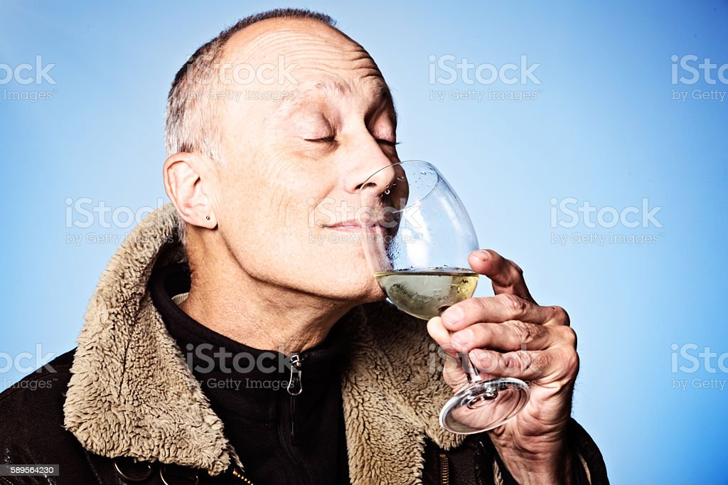 Mature man sniffs glass of white wine appreciatively, eyes closed stock photo