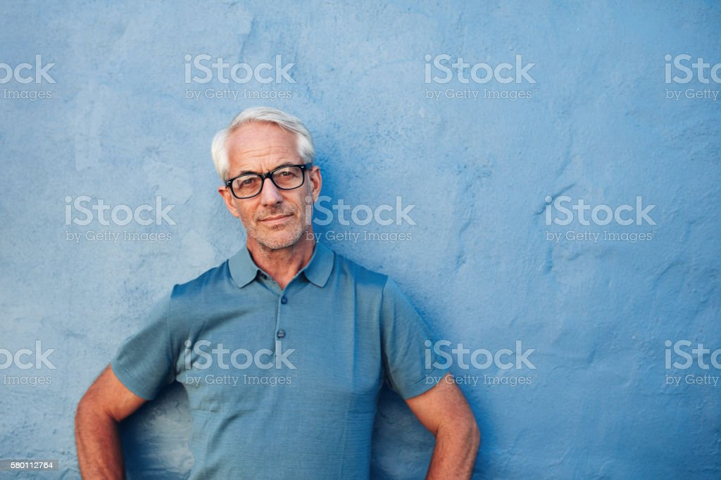 Mature man standing against a blue wall stock photo