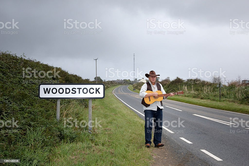 Mature man standing at roadside with guitar stock photo
