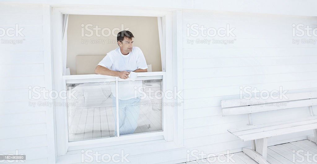 Mature man standing at window looking outdoors royalty-free stock photo