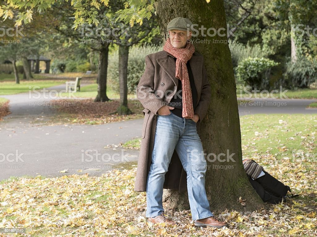 Mature man standing under a tree outdoors. stock photo