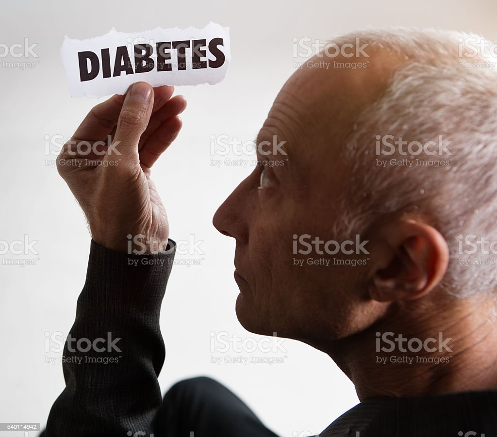 Mature man studies Diabetes printout, frowning and serious stock photo