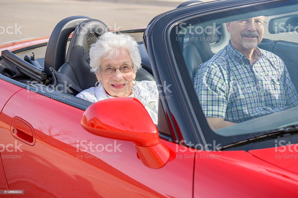Mature man takes widow mother for ride in red convertible stock photo