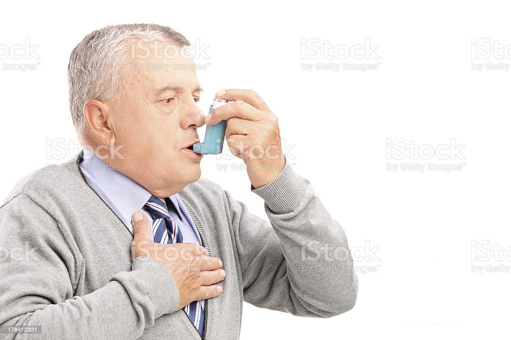 Mature man taking asthma treatment stock photo