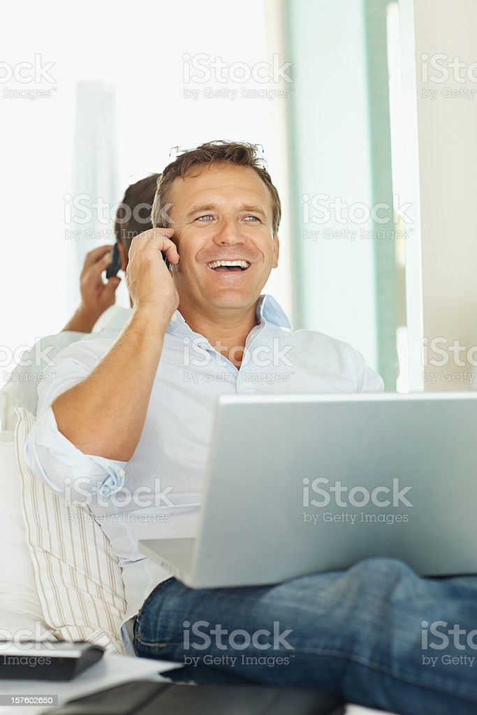 Mature man talking on cellphone while using laptop royalty-free stock photo