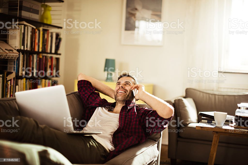 Mature man talking on mobile phone at home stock photo