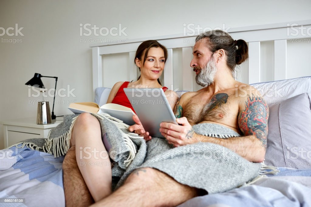 Mature man talking with pregnant wife in their bedroom stock photo