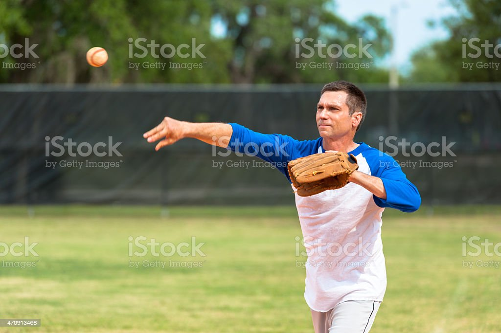 Mature man throwing baseball stock photo