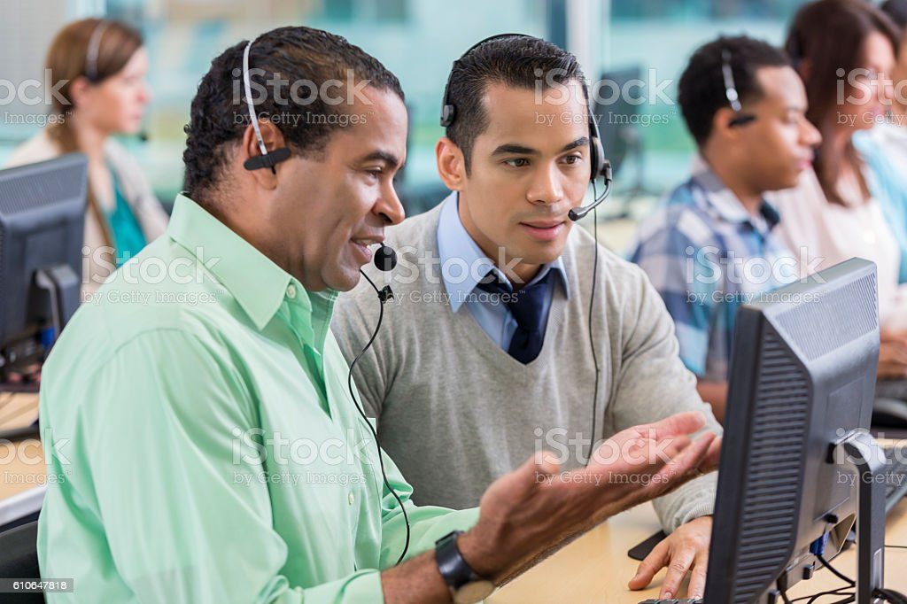 Mature man trains new employee in call center stock photo