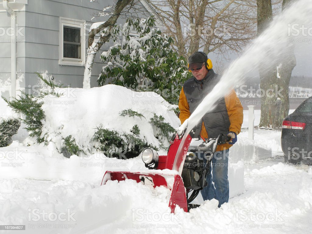 Mature man using a snow blower. stock photo