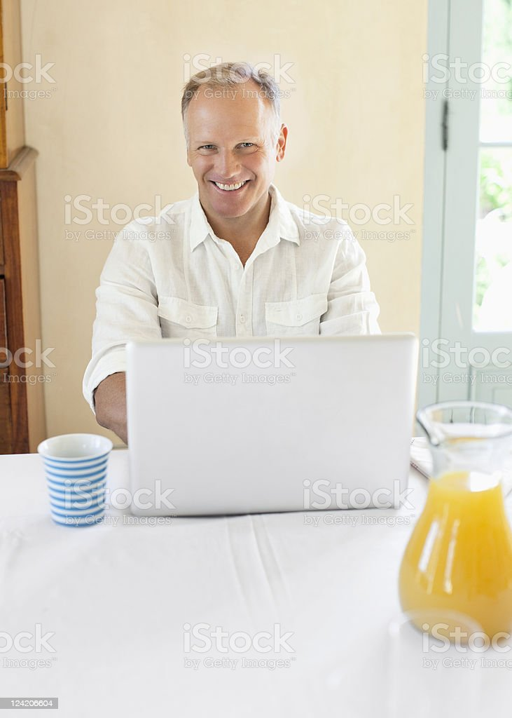 Mature man using laptop at breakfast table royalty-free stock photo