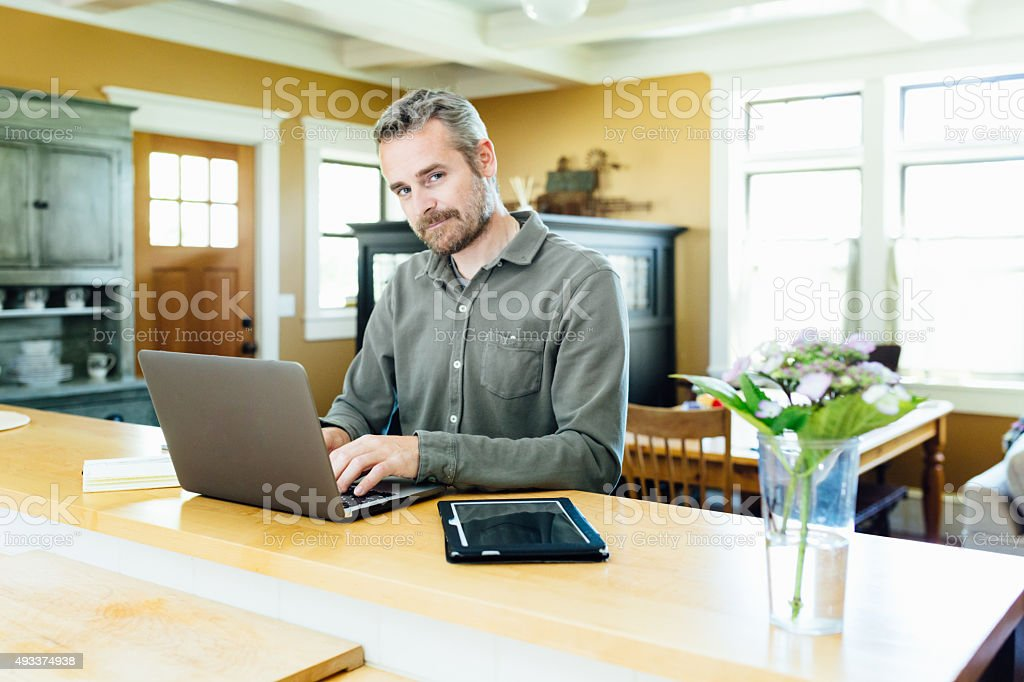 Mature man using laptop at home. stock photo