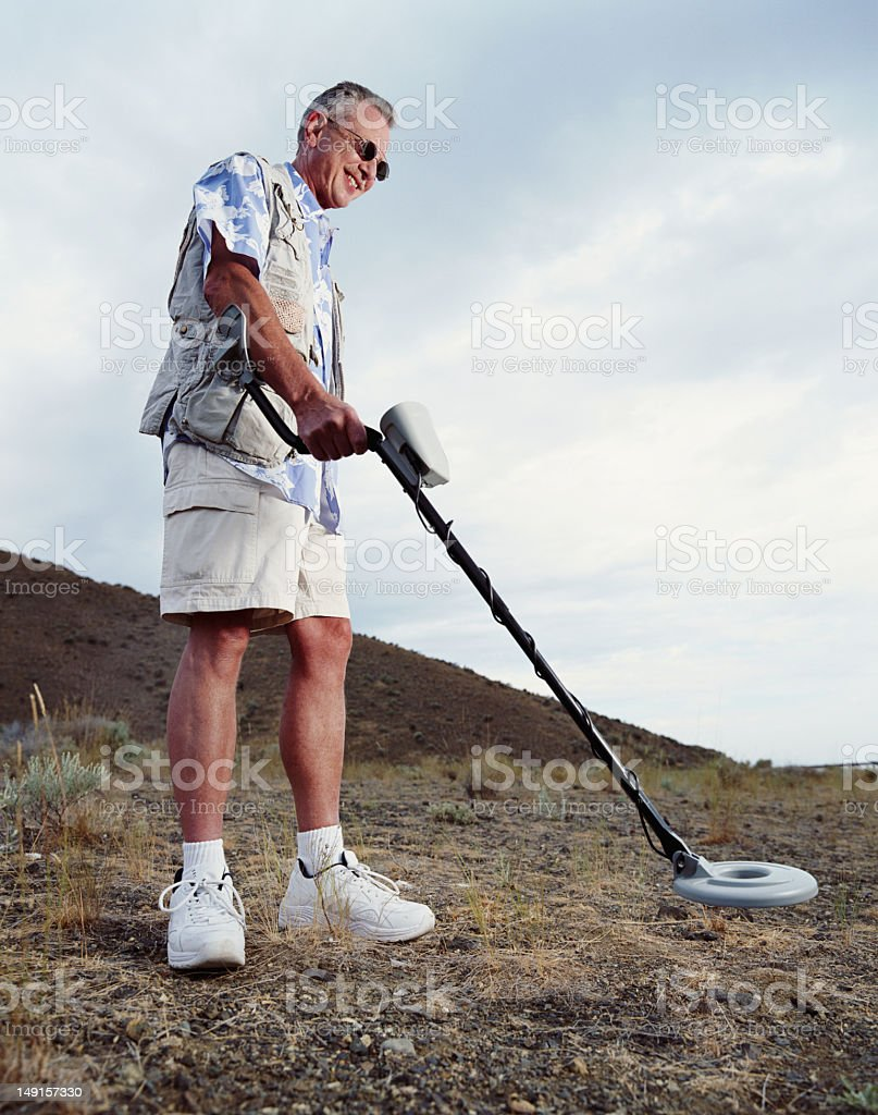 Mature man using metal detector, smiling royalty-free stock photo