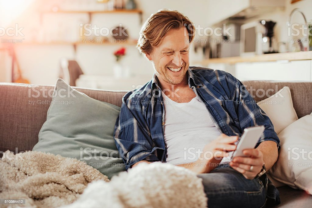 Mature man using mobile phone at home stock photo