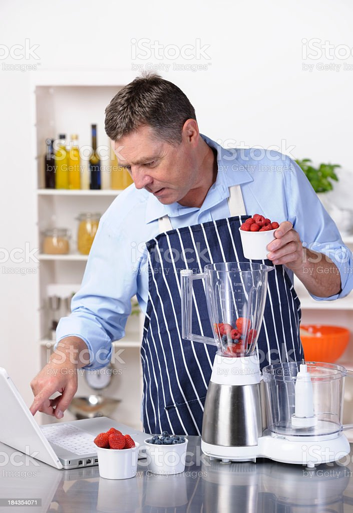 Mature Man Using Online Recipe To Make Healthy Drink/ dessert royalty-free stock photo