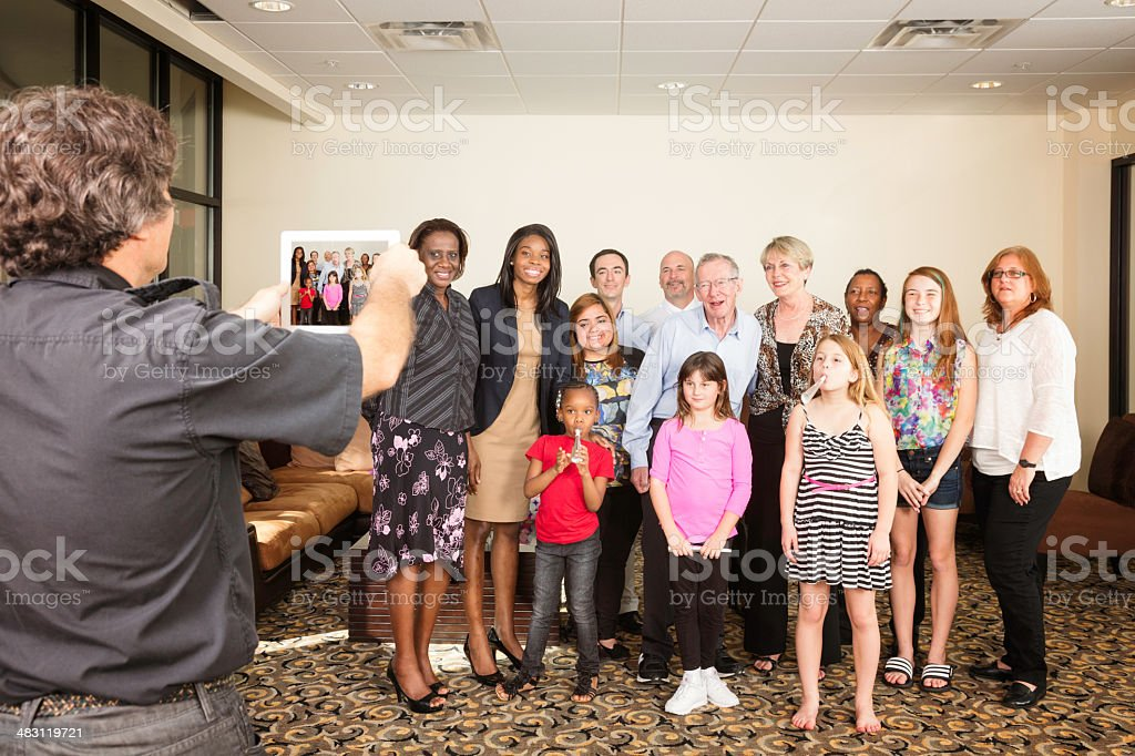 Mature man using tablet to photograph family at birthday party royalty-free stock photo