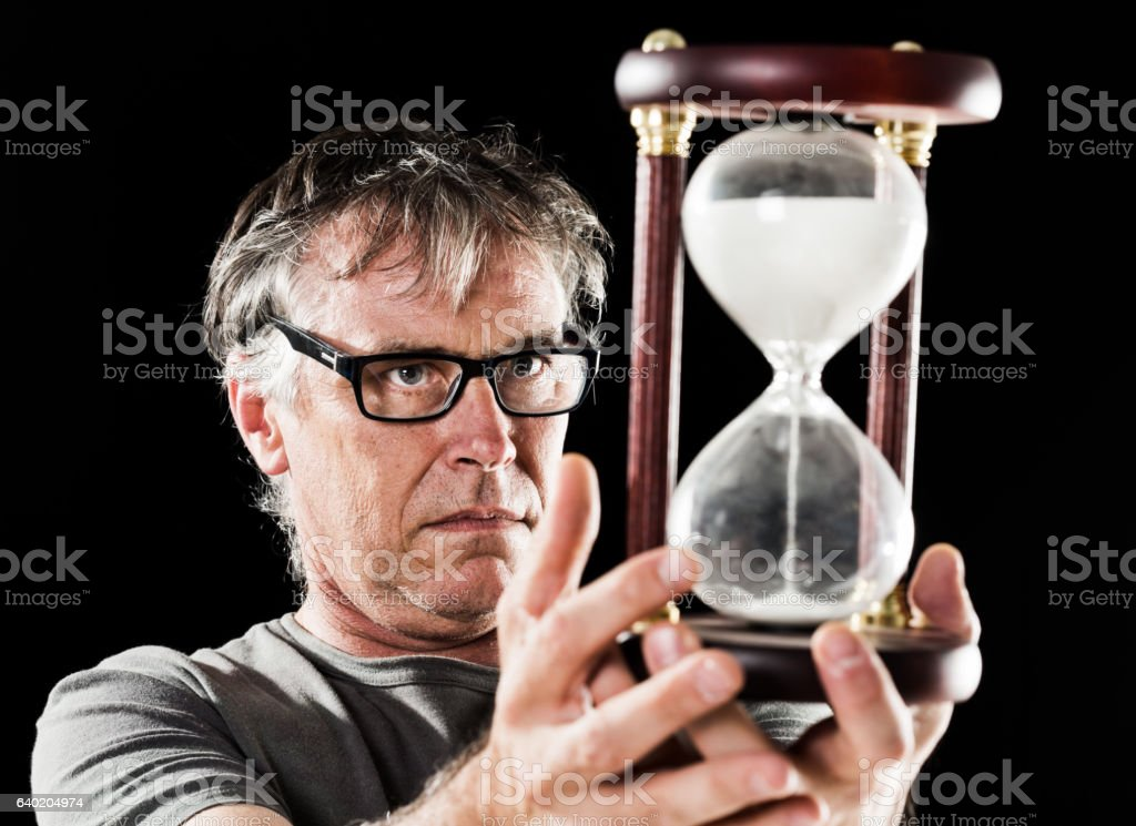 Mature man watches time passing in hourglass with worried expression stock photo