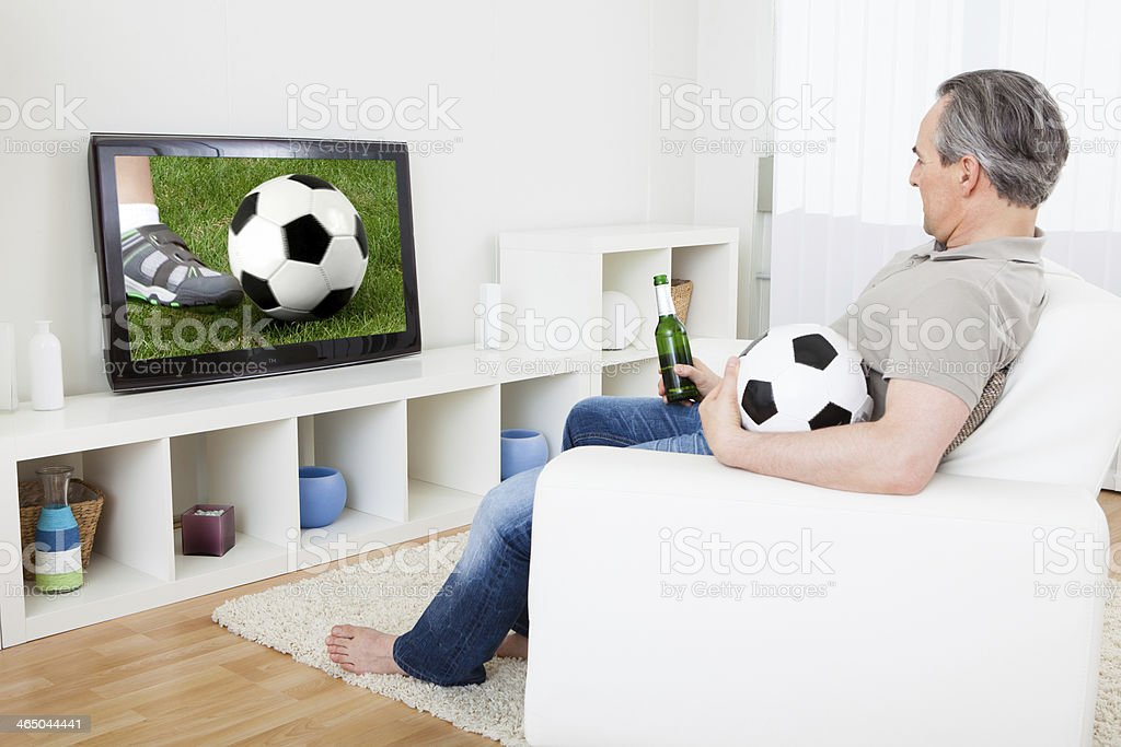 Mature man watching football on television stock photo