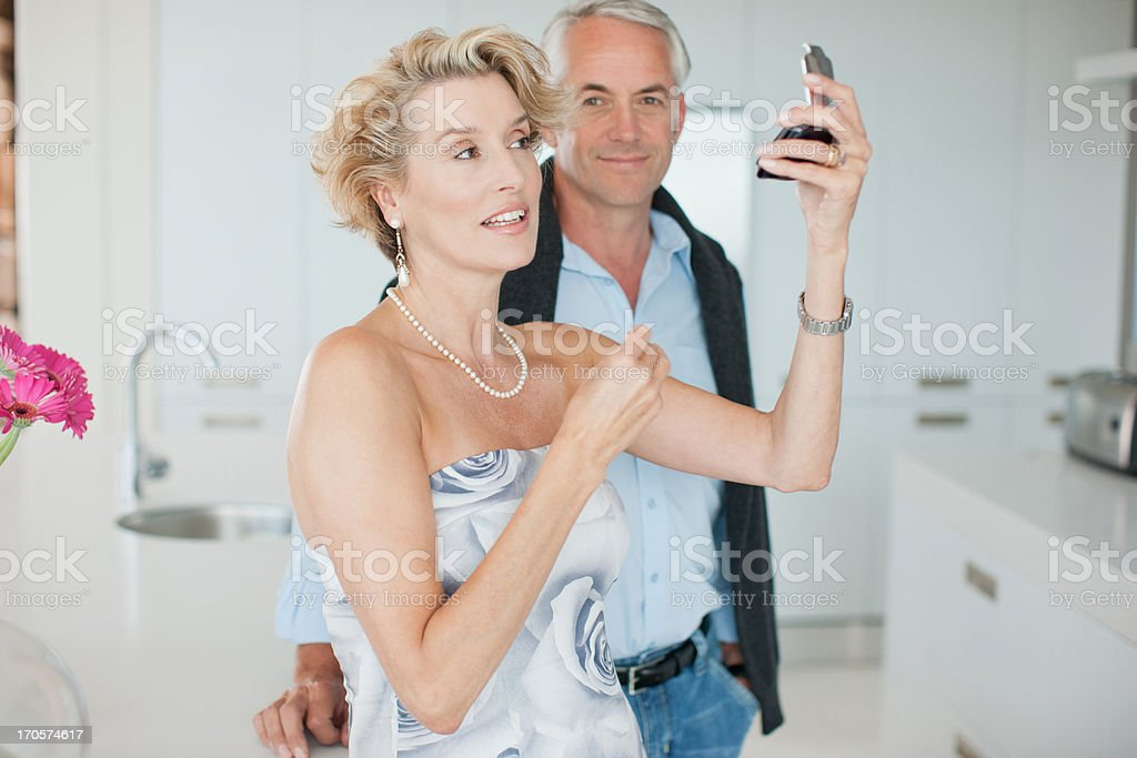 Mature man watching woman apply makeup stock photo
