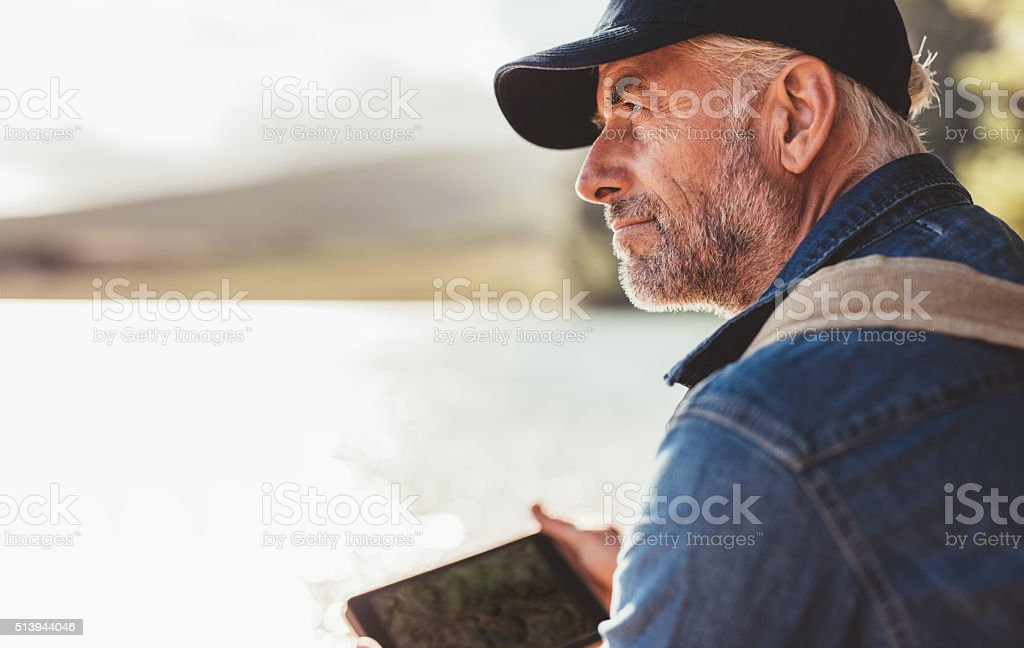 Mature man wearing cap sitting at a lake stock photo