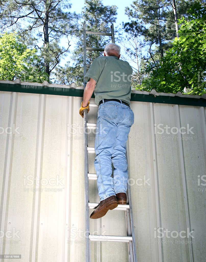 Mature Man wearing work clothes on ladder royalty-free stock photo