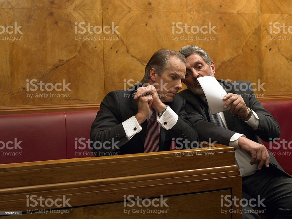 Mature man whispering to colleague in pew stock photo