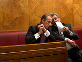 Mature man whispering to colleague in pew