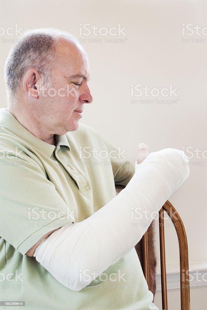 mature man with a broken arm in a cast sitting royalty-free stock photo