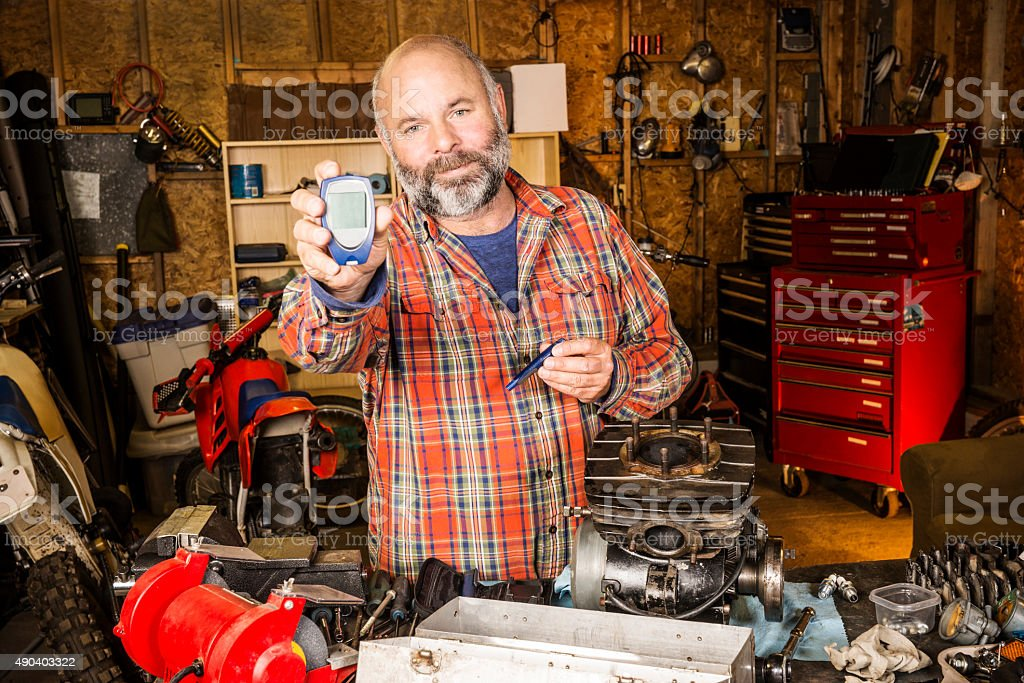 Mature man with a diabetes glaucometer in his garage stock photo