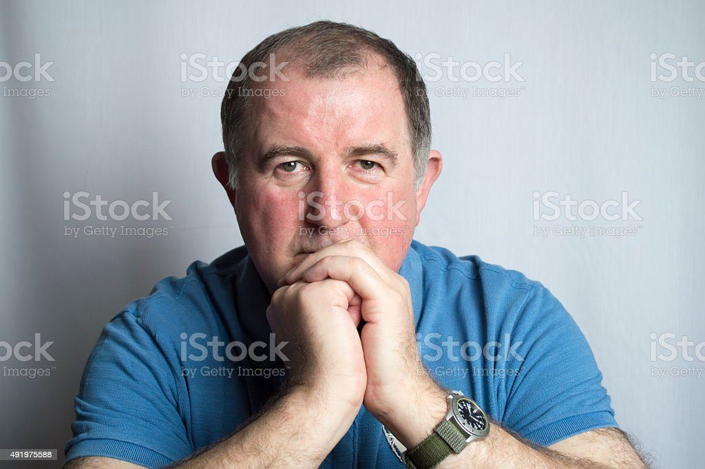 Mature man with a worried and serious facial expression stock photo