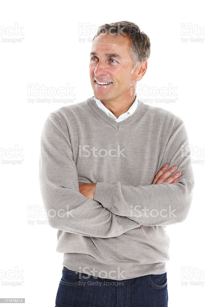 Mature man with arms folded looking away smiling against white stock photo