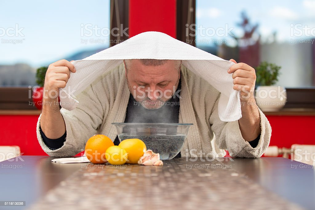 Mature man with colds and flu. Inhalation of herbs stock photo