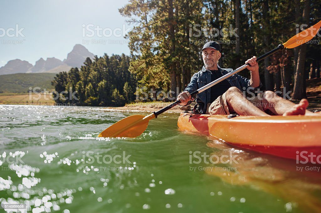 Mature man with enjoying kayaking in a lake stock photo