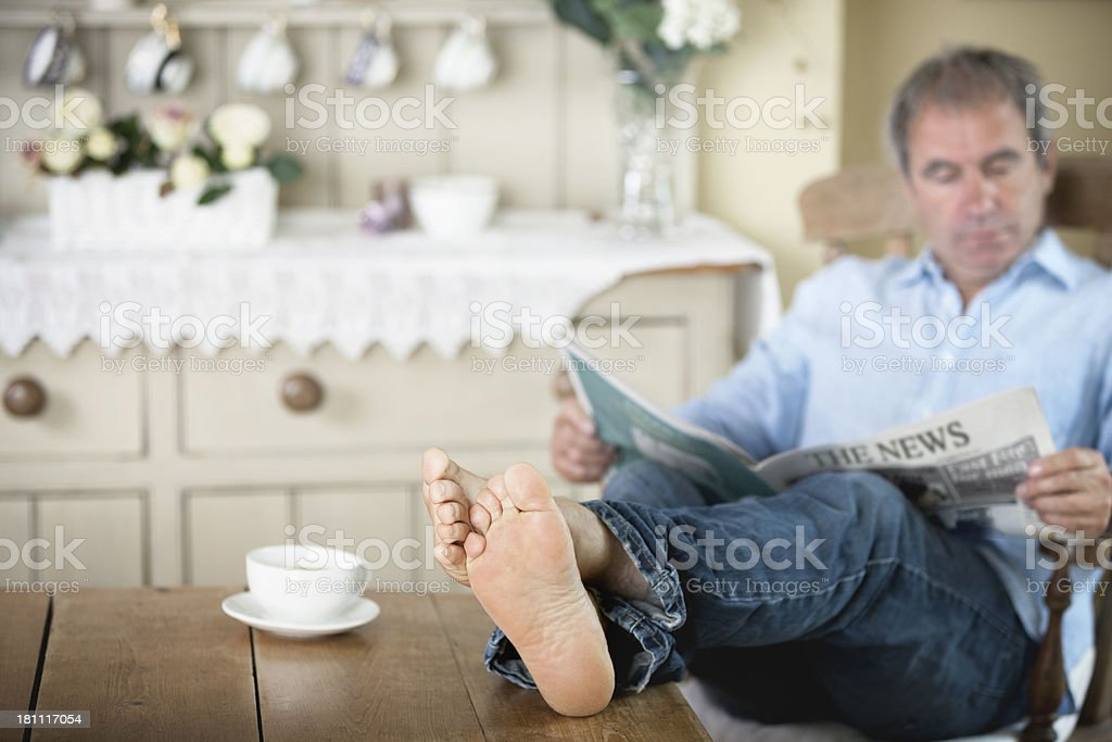 Mature man with feet up reading newspaper royalty-free stock photo