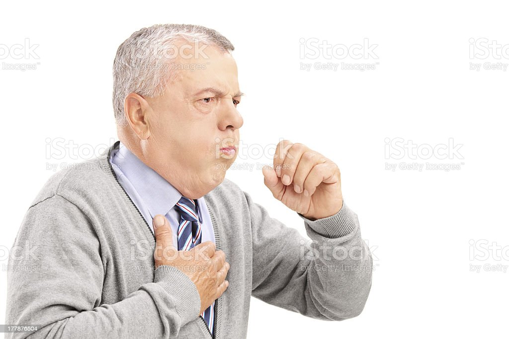 A mature man with gray hair coughing into his hand stock photo