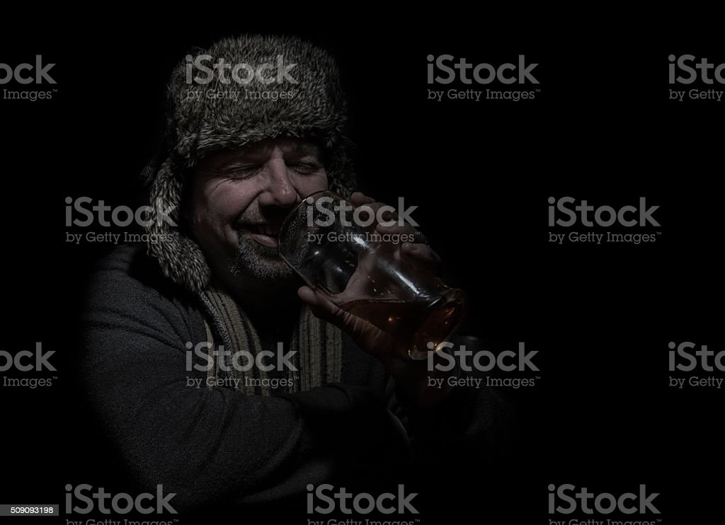 Mature man with hat and scarf, drinking beer stock photo