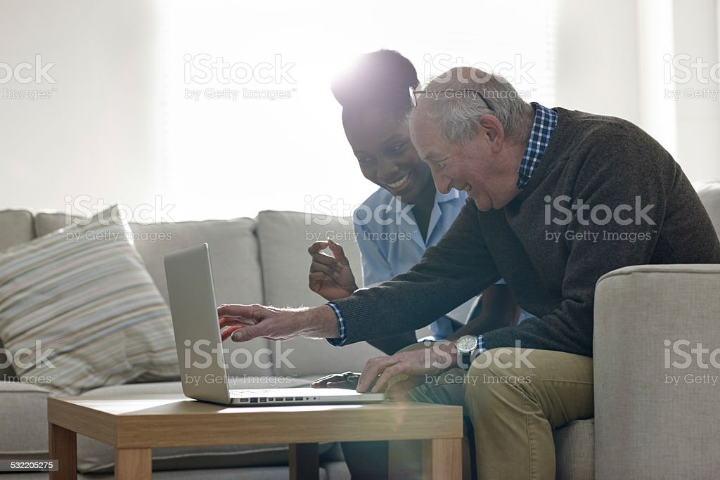 Mature man with his nurse looking at the laptop stock photo