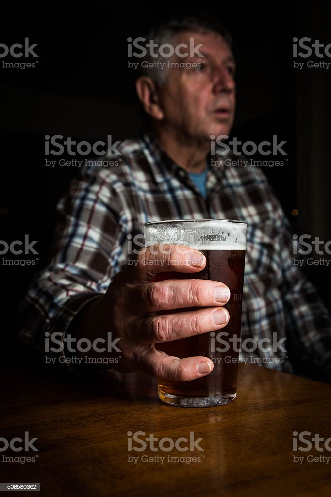 mature man with large glass of lager - UK stock photo