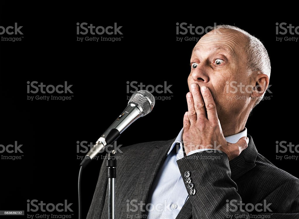 Mature man with microphone gets stage fright and panics stock photo