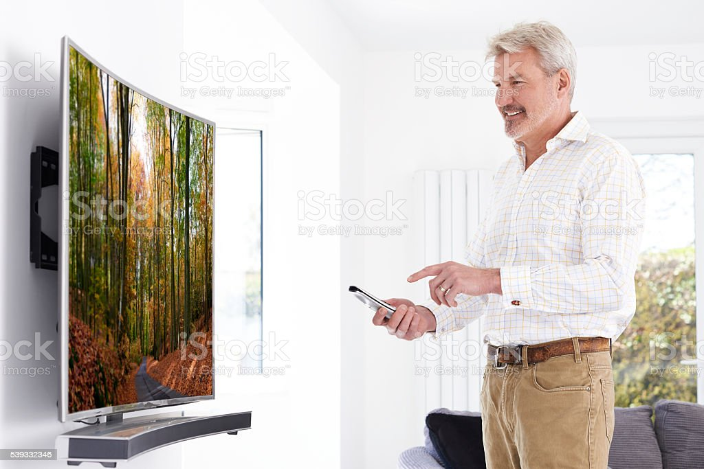 Mature Man With New Curved Screen Television At Home stock photo