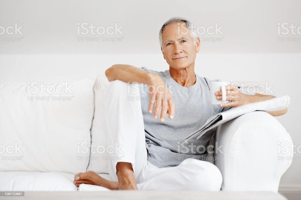Mature man with newspaper while holding a cup of  coffee royalty-free stock photo