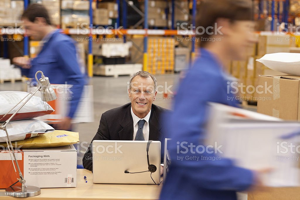 Mature man with workers working in warehouse stock photo