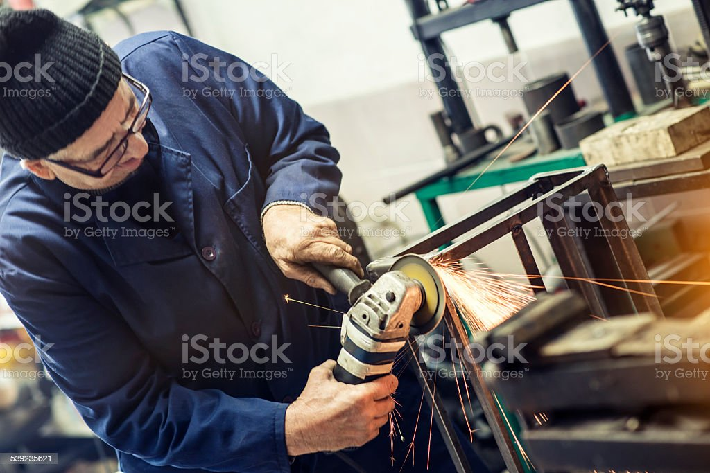 Mature Man Worker Grinding Metal with Angle Gringer in Workshop stock photo