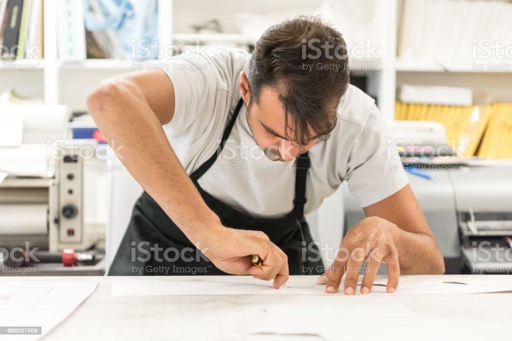 Mature man working at his printing-graphic design shop stock photo