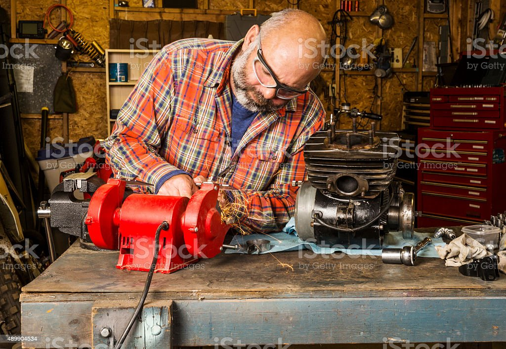 Mature man working in the garage on a motorcycle engine stock photo