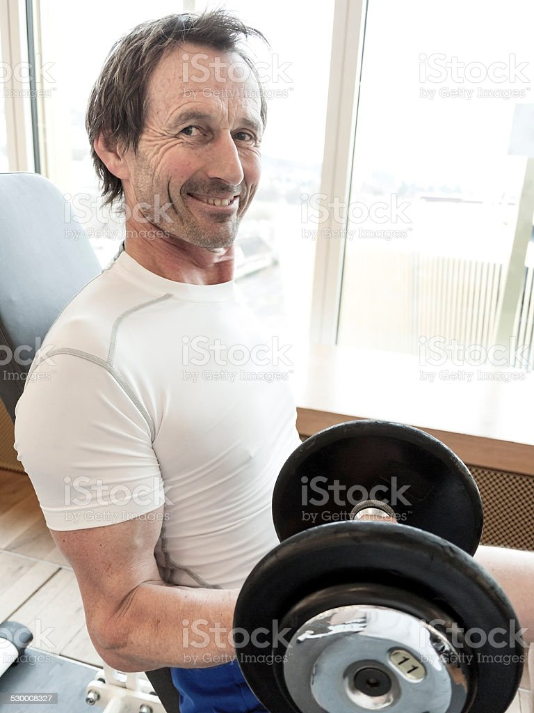 Mature Man Working out doing Bicep Curls at the Gym stock photo