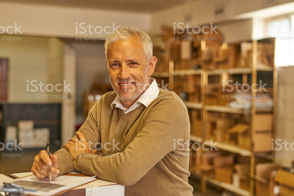 Mature man working with docs in warehouse stock photo