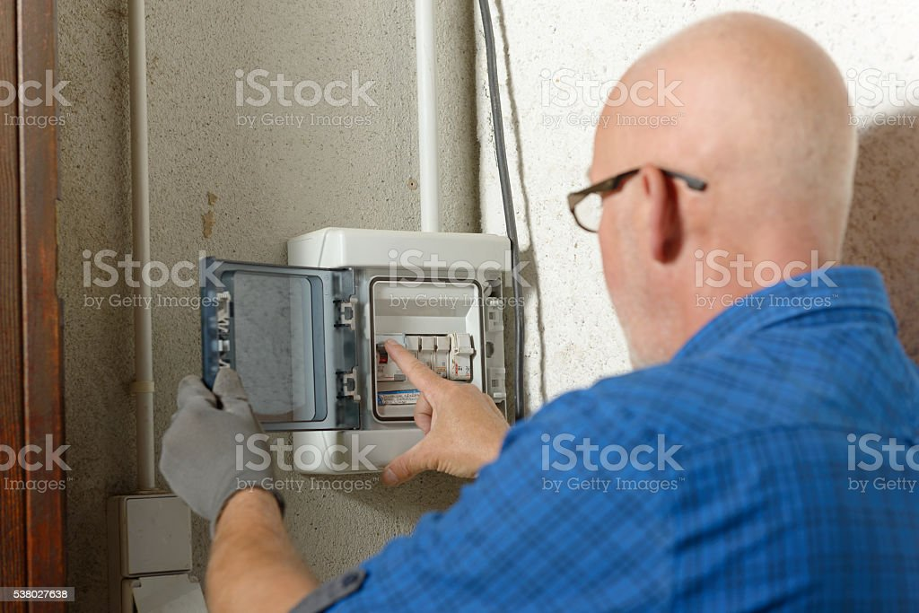 mature man working with electric box at house stock photo