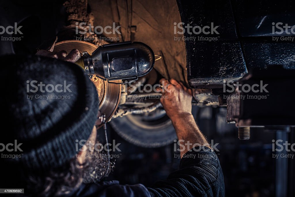 Mature mechanic at repair service station inspecting car suspen stock photo
